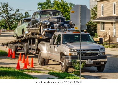 """ELBURN, IL/USA - JULY 25, 2018: Two vintage American cars are about to be offloaded in this small town for filming of """"Lovecraft Country,"""" a dramatic TV series set in the 1950s to be aired on HBO."""