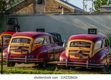 """ELBURN, IL/USA - JULY 25, 2018: Two vintage Packards, with a third parked nearby, stand ready for filming of """"Lovecraft Country,"""" a dramatic TV series set in the 1950s to be aired on HBO."""