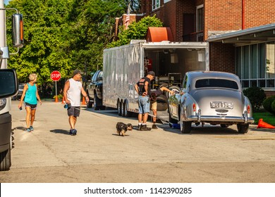 """ELBURN, IL/USA - JULY 25, 2018: A couple and their dog watch two handlers inspect a vintage car before a scene is filmed for """"Lovecraft Country,"""" a TV series set in the 1950s to be aired on HBO."""