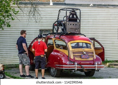"""ELBURN, IL/USA - JULY 25, 2018: Two crew members discuss a classic Packard customized with a rooftop rig before local filming of """"Lovecraft Country,"""" a TV series set in the 1950s to be aired on HBO."""