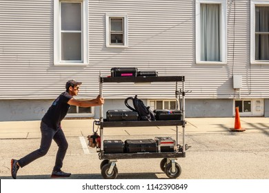 """ELBURN, IL/USA - JULY 25, 2018: An assistant pushes a loaded equipment cart along a downtown sidestreet before local filming of """"Lovecraft Country,"""" a TV series set in the 1950s to be aired on HBO."""