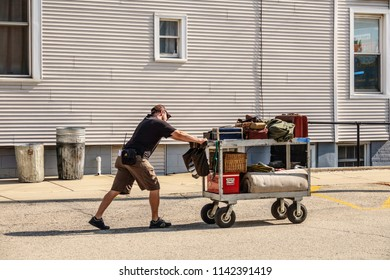"""ELBURN, IL/USA - JULY 25, 2018: A crew member pushes a cart loaded with props along a downtown sidestreet before local filming of """"Lovecraft Country,"""" a TV series set in the 1950s to be aired on HBO."""