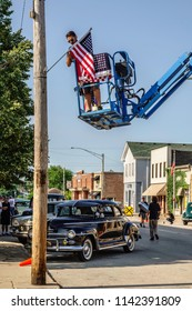 """ELBURN, IL/USA - JULY 25, 2018: A decorator on an aerial work platform hangs a 48-star American flag on a Main Street location of """"Lovecraft Country,"""" a TV series set in the 1950s to be aired on HBO."""