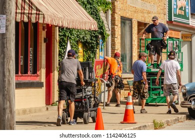 """ELBURN, IL/USA - JULY 25, 2018: An assistant pushes a cart full of electrical equipment along a sidewalk before local filming of """"Lovecraft Country,"""" a TV series set in the 1950s to be aired on HBO."""