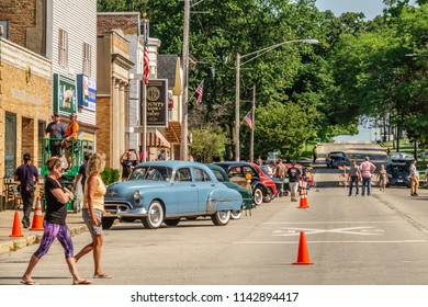 "ELBURN, IL/USA - JULY 25, 2018: Two women onlookers cross Main Street during preparations for local filming of ""Lovecraft Country,"" a TV series set in the 1950s to be aired on HBO."