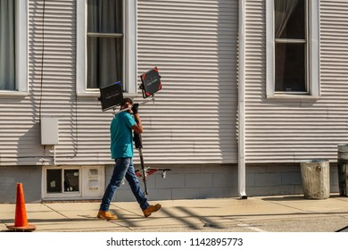 """ELBURN, IL/USA - JULY 25, 2018: A technical assistant carries a piece of video equipment up a side street for local filming of """"Lovecraft Country,"""" a TV series set in the 1950s to be aired on HBO."""