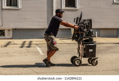 """ELBURN, IL/USA - JULY 25, 2018: A technical assistant pushes a cart loaded with video equipment toward Main Street for local filming of """"Lovecraft Country,"""" a dramatic pilot for HBO set in the 1950s."""