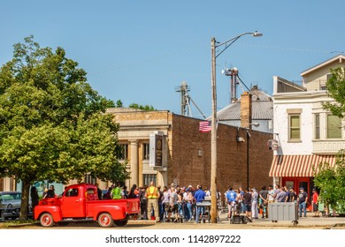 """ELBURN, IL/USA - JULY 25, 2018: Production crew and security guards on Main Street listen to final instructions before local filming of """"Lovecraft Country,"""" a dramatic pilot for HBO set in the 1950s."""