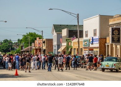 """ELBURN, IL/USA - JULY 25, 2018: Production crew members and others meet on Main Street for final instructions before local filming of """"Lovecraft Country,"""" a dramatic pilot for HBO set in the 1950s."""