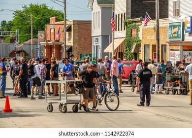 """ELBURN, IL/USA - JULY 25, 2018: Production crew members disperse after an onsite meeting for final instructions before local filming of """"Lovecraft Country,"""" a dramatic pilot for HBO set in the 1950s."""