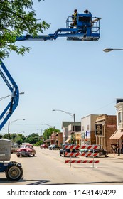 """ELBURN, IL/USA - JULY 25, 2018: A camera operator on an aerial work platform on Main Street films a scene with classic cars for """"Lovecraft Country,"""" a dramatic pilot for HBO set in the 1950s."""