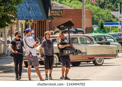 """ELBURN, IL/USA - JULY 25, 2018: A cameraman, sound technician, and two assistants record a scene on Main Street for """"Lovecraft Country,"""" a dramatic pilot for HBO set in the 1950s."""