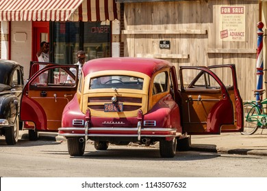 """ELBURN, IL/USA - JULY 25, 2018: An actor contemplates the front of a classic Packard that will arrive outside a fictitious diner in """"Lovecraft Country,"""" a dramatic pilot for HBO set in the 1950s."""