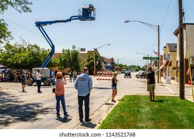 """ELBURN, IL/USA - JULY 25, 2018: Onlookers await the start of a scene with classic cars on Main Street during filming of """"Lovecraft Country,"""" a dramatic pilot for HBO set in the 1950s."""