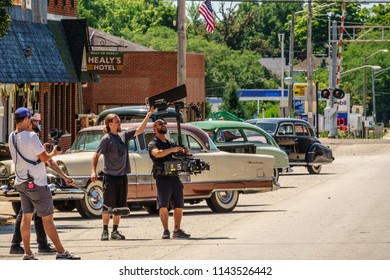 """ELBURN, IL/USA - JULY 25, 2018: A camera operator checks settings on video equipment during filming of """"Lovecraft Country,"""" a dramatic pilot for HBO set in the 1950s."""