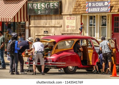 """ELBURN, IL/USA - JULY 25, 2018: Production crew members check interior details of a classic Packard parked on Main Street for filming of """"Lovecraft Country,"""" a dramatic pilot for HBO set in the 1950s."""