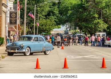 """ELBURN, IL/USA - JULY 25, 2018: Production crew members congregate by equipment carts on Main Street before filming scenes for """"Lovecraft Country,"""" a dramatic made-for-TV HBO movie set in the 1950s."""