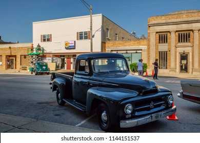 """ELBURN, IL/USA - JULY 25, 2018: A shiny vintage pickup truck stands parked in morning shadow on Main Street before local filming of """"Lovecraft Country,"""" an HBO TV series set in the 1950s."""