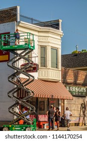 """ELBURN, IL/USA - JULY 25, 2018: A decorator makes final touch-ups high on a hydraulic lift on Main Street before local filming of """"Lovecraft Country,"""" a TV series set in the 1950s to be aired on HBO."""