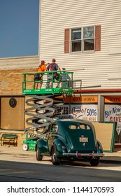 """ELBURN, IL/USA - JULY 25, 2018: A crew member points out something to a fellow worker above a storefront on Main Street before local filming of """"Lovecraft Country,"""" an HBO TV series set in the 1950s."""