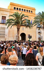 Elche, Alicante, Spain-July 15, 2019: People protesting with a minute of silence for the murder of a woman by sexist violence in the town hall of Elche