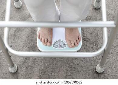 Eldely female standing on weight scale , her weight measure  54