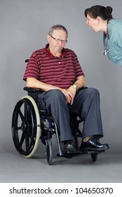 Elder abuse concept: senior man with head down in a wheelchair as a crazy nurse or other health care worker is yelling at him