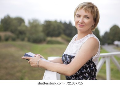 Elder aged woman on her free time walking relaxing in park. Smiling cheerfully, reading a book. Sunny day. Copy space