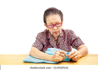 Elder Asian lady age between 80-85 years old is sewing a cloth professionally.  Isolated on white background.