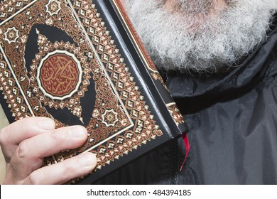 elder black dressed man with a grey full beard holding a quran with the symbol of islam: In arabic letters is written: There is no god but Allah and Muhammad is the messenger of Allah.