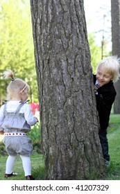 Elder brother is hiding behind a tree from little sister.