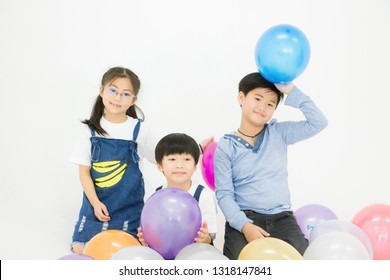 Elder brother, elder sister and younger brother are taking pictures together after playing balloons In a white background studio. Concept of unity, harmony and good relationships in the family.