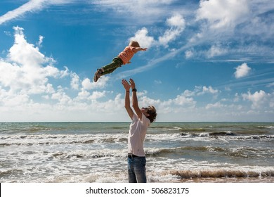 The elder brother throws his younger brother on the beach against the backdrop of the sea. Happy carefree childhood.