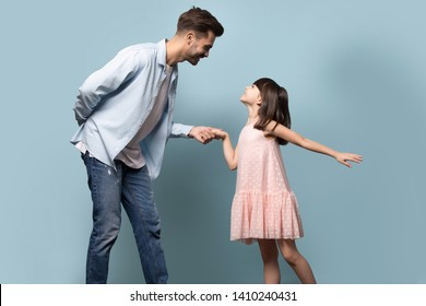 Elder brother younger sister dancing waltz enjoy time together, loving young father gentleman and little daughter princess in pink dress standing holding hands family pose isolated on blue background