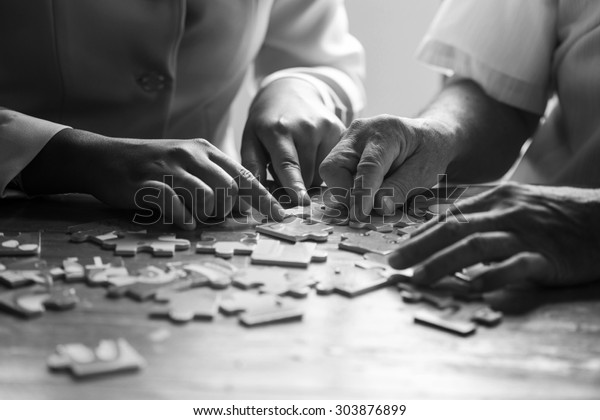 Elder care nurse playing jigsaw puzzle with senior man in nursing home. black and white