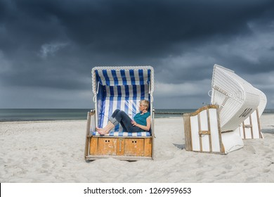 elder caucasian woman relaxing in a roofed wicker beach chair at the baltic sea under a dark cloudy sky, germany, Europe