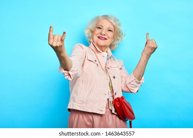 elder cheerful positive gorgeous lady making rock sign, isolated blue background, studio shot. body language, lifestyle, free time, spare time
