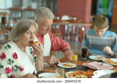 Elder couple eating pizza with boy in cafe