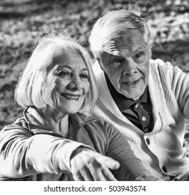 Elder couple enjoying outdoor life with woman pointing finger.