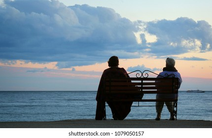 Elder couple couple sitting on a seaside bench enjoying the sunset over the sea