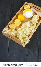 elder flower juice ingredients on wooden tray, black wood table background