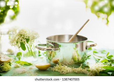 Elder flowers syrup cooking preparation. Pot with wooden spoon on kitchen table with sugar, lemon and elderflowers. Healthy seasonal natural food concept. Copy space for your recipes