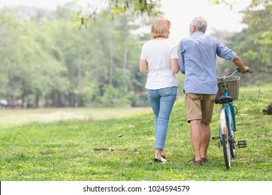 Elder healthy leisure lifestyle,Senior couple walking their bike along happy talking in the park, rear view of an older caucasian walk in a park