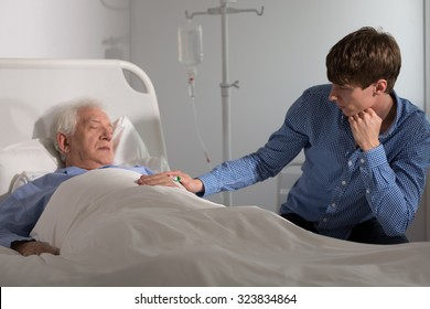 Elder ill man sleeping and a relative holding his hand