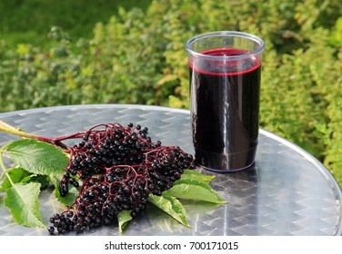 elder juice and elder berries on a  patio table outdoors, green background