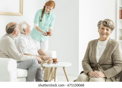 Elder lady sitting and smiling at senior's house