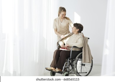 Elder lady in a wheelchair sitting with book and blanket
