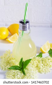 Elder lemonade - healthy and refreshing summer drink. Close up of homemade elderflower syrup in a bottle with elder flowers. Summer drink Hugo Champagne drink with elderflower syrup, mint and lime.