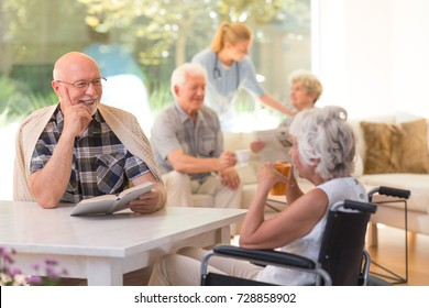 Elder man with a book talking to disabled woman drinking tea