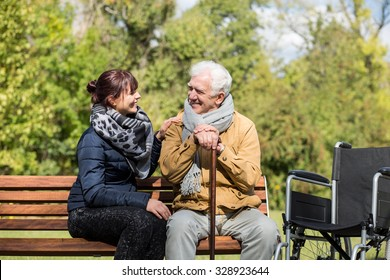 Elder man and carer in the park